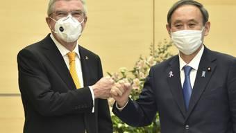 Treffen im Hinblick auf Tokio 2021: IOC-Präsident Thomas Bach und der japanische Ministerpräsident Yoshihide Suga posieren mit Mundschutzmasken