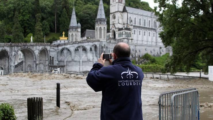 Ein Wächter macht ein Foto des überschwemmten Wallfahrtsorts.