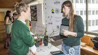 Am Nachhaltigkeitsbazar präsentiert eine Studentin die alternative Suchmaschine Ecosia.
