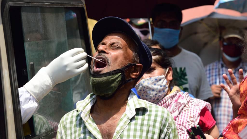 Ein Mitarbeiter des indischen Gesundheitswesens sitzt in einem Auto und entnimmt durch das Fenster einem Mann für einen Corona-Test einen Abstrich. Foto: Sumit Sanyal/SOPA Images via ZUMA Wire/dpa