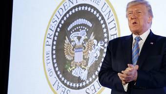 Doppelköpfiger Adler, Golfschläger und Geldscheine statt Pfeile und Zweig: US-Präsident Donald Trump vor dem gefälschten Präsidenten-Siegel an einer Studentenveranstaltung.