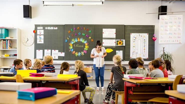 Erstklässler am ersten Schultag. Rechts an der Wandtafel hängt bereits die Anlauttabelle, die zum Erlernen des lautgetreuen Schreibens dient und weiterhin im Unterricht eingesetzt werden darf.