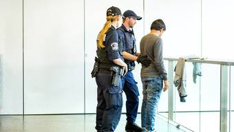 Kantonspolizisten suchen bei einem Asylbewerber nach einem Messer. (Archiv)