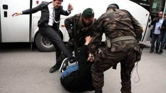 Eine Berater von Premierminister Erdogan tritt einen Demonstranten.