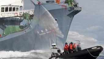 """Ein japanisches Walfangschiff richtet im Februar 2011 einen Wasserwerfer auf ein Schlauchboot mit Aktivisten bzw. """"Piraten"""" der Anti-Walfang-Organisation Sea Shephe"""