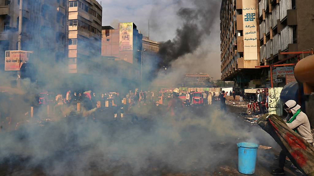 Ein Demonstrant in Bagdad versucht sich mit einer Decke vor Tränengas-Granaten zu schützen. Seit Beginn der Proteste Anfang Oktober wurden laut Uno bereits etwa 20 Menschen durch Tränengas-Granaten getötet. Den meisten Opfern zertrümmerten die Geschosse den Schädel.