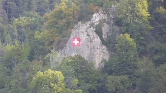 Abgehängt, kurz durch eine Deutschlandfahne ersetzt und wieder aufgehängt: Schweizerfahne an der Weissen Fluh. Bild: Roger Lange