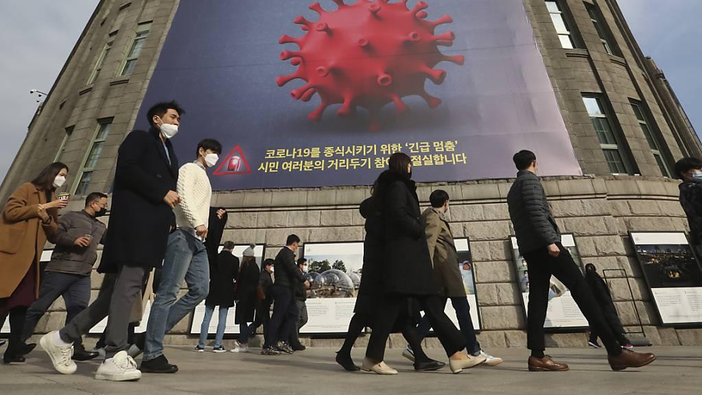 Menschen, die Gesichtsmasken tragen, gehen vor dem Rathaus von Seoul unter einem Transparent, das auf eine verstärkte soziale Distanzierungskampagne hinweist, vorbei.
