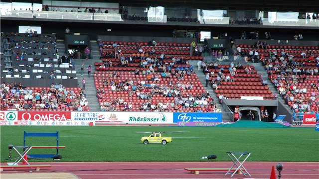 Kleine Elektroautos, die aussehen wie Riesenspielzeug, fahren die Speere nach dem Wurf zurück zu den Athleten.