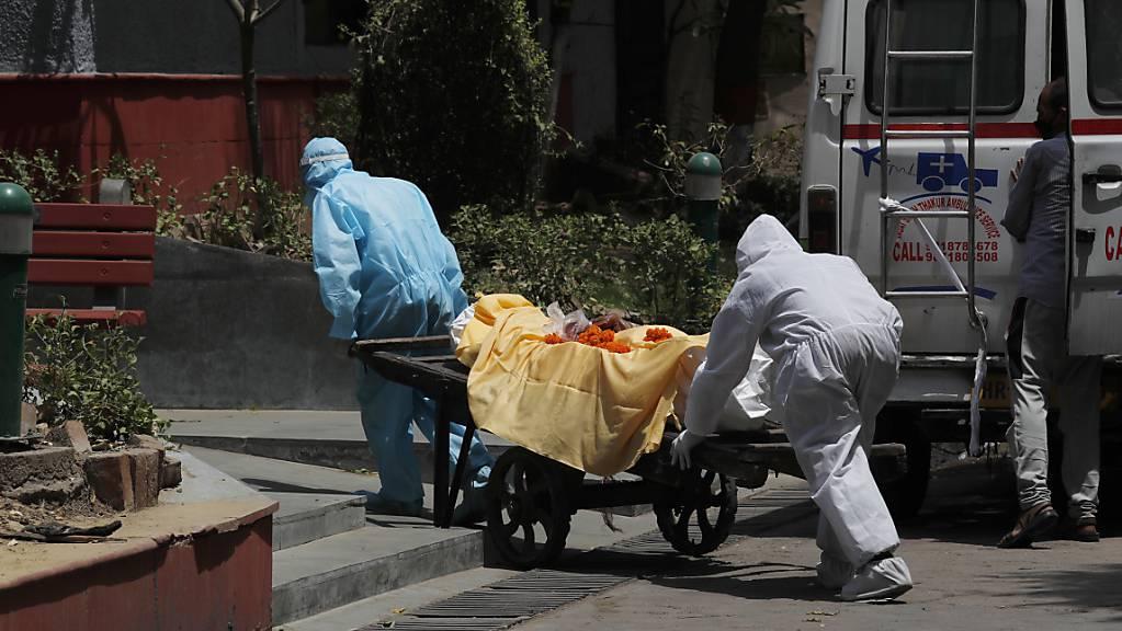 Gesundheitspersonal in Schutzanzügen befördert die Leiche eines Mannes, der an Covid-19 gestorben ist, auf einem Handkarren zur Einäscherung. Foto: Manish Swarup/AP/dpa