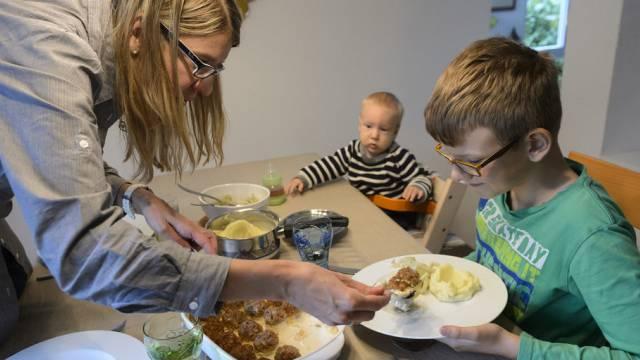 Eine Mutter mit ihren Kindern beim Mittagessen (Symbolbild)