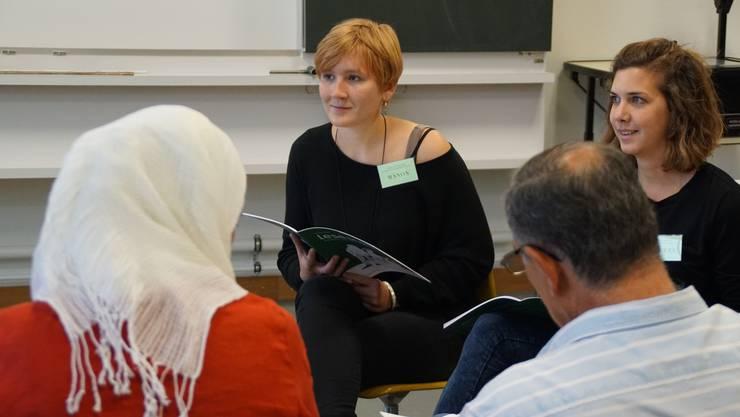 Manon Kaiser und Michèle Bichsel lesen eine Geschichte mit den Flüchtlingen.