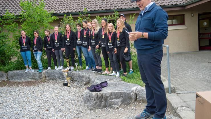 Die Damen des UHC Oekingen mit Medaillen und Gewinnerpokalen.