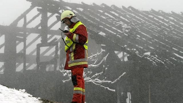 Ein Feuerwehrmann steht vor dem abgebrannten Haus in Steinerberg