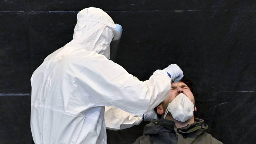 Ein Mitarbeiter in Schutzkleidung führt bei einem Mann einen Abstrich für einen Corona-Test durch. Foto: Herbert Neubauer/APA/dpa
