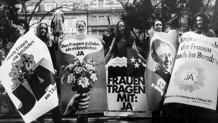 Mit Plakaten werben Frauen 1971 im Vorfeld der eidgenössischen und kantonalen Abstimmung für das Frauenstimmrecht.