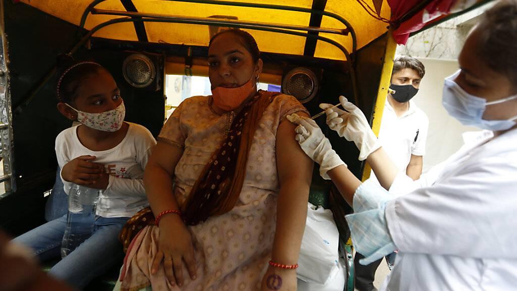 Eine Mitarbeiterin des Gesundheitswesens impft in Ahmedabad eine Frau gegen das Coronavirus. Foto: Ajit Solanki/AP/dpa