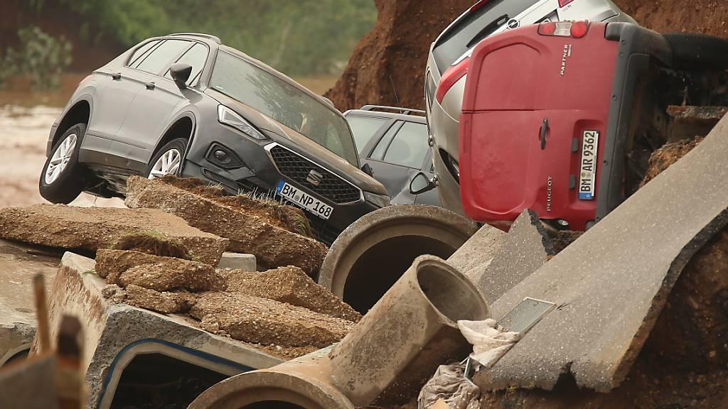 Autos liegen in einem ausgespülten Teil der nordrhein-westfälischen Stadt Erftstadt. Foto: David Young/dpa