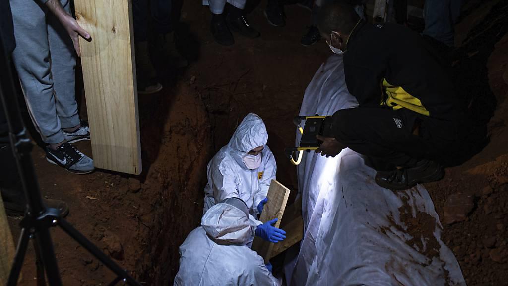 dpatopbilder - Menschen in Schutzkleidung nehmen in Johannesburg an einer Beerdigung einer an Corona gestorbenen Person teil. Südafrika ist eines der Länder auf dem Kontinent mit den meisten Todesfällen in Zusammenhang mit dem Coronavirus. Foto: Ali Greeff/AP/dpa