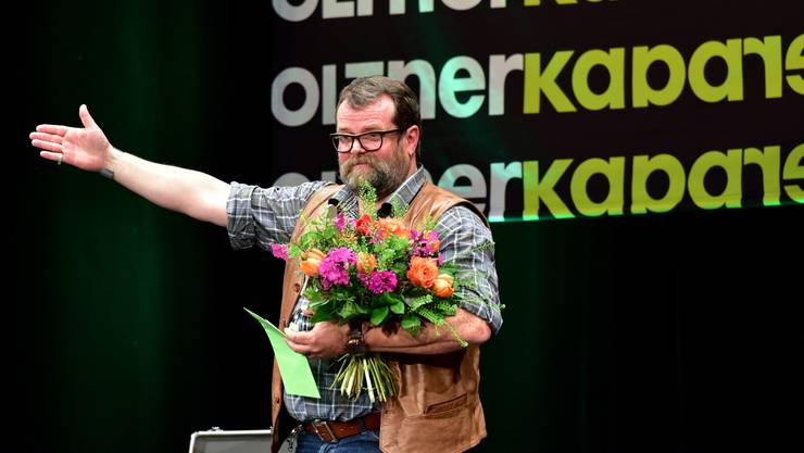 Jochen Malmsheimer mit Blumen auf der Bühne.