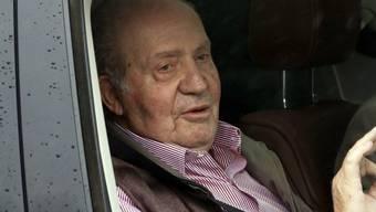 Der emeritierte spanische König Juan Carlos winkt beim Verlassen des Spitals aus dem Auto. Er hatte sich am Samstag ein künstliches Kniegelenk ersetzen lassen müssen.