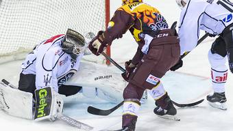Luganos Goalie Sandro Zurkirchen hatte viel zu tun im Match gegen Genf-Servette. Hier muss er sich gegen Tommy Wingels wehren. Rechts Alessio Bertaggia