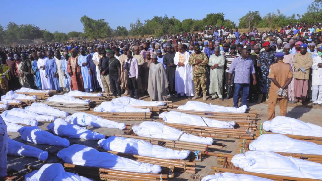 Menschen stehen bei einer Beerdigung vor den Leichen der Personen, die bei einem Angriff ums Leben gekommen sind.