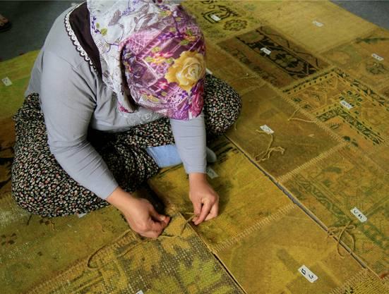 Eine Frau näht die Patchworkteile zusammen.