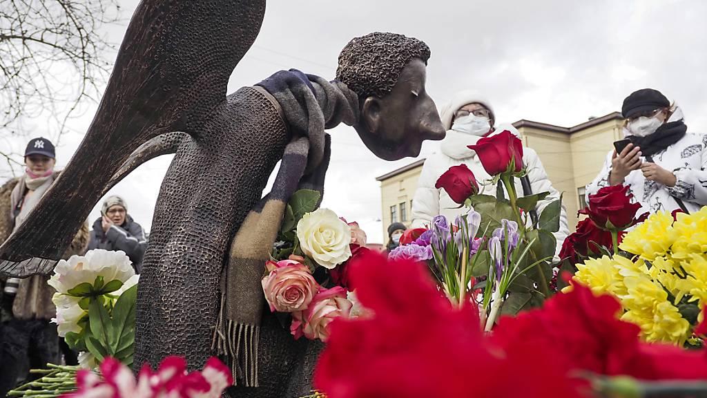 ARCHIV - Menschen stehen vor der mit Blumen umringten Skulptur «Trauriger Engel» des Bildhauers Shustrov, während der Eröffnung einer Gedenkstätte für medizinische Mitarbeiter, die in St. Petersburg an einer Corona-Infektion gestorben sind (Archivbild). Foto: Dmitri Lovetsky/AP/dpa