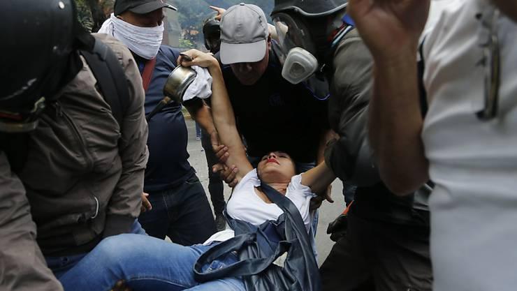 Helfer tragen eine Frau nach einer Tränengasattacke weg.