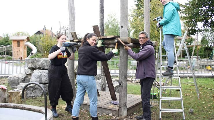Viviane Wernli, Yasmina Jörger und Jill Keiser (von links) werden von Chrüzi-Mitarbeiter Andi Kohler beim Bau des neuen Geissenturms unterstützt.