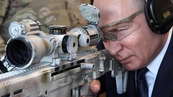 Russlands Präsident Putin medienwirksam als treffsicherer Schütze an einer Kalaschnikow.