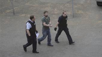 Der Angeklagte wird in Handschellen von zwei Justizbeamten zum Gerichtsgebäude gebracht.