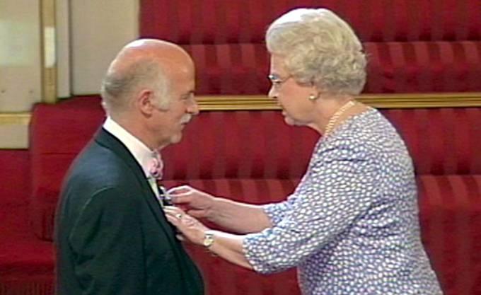 Queen Elisabeht II schlägt Anton Mosimann zum Ritter und steckt ihm den Orden an.