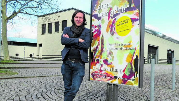 Ausstellungsmacher Martin Steiner vor dem Plakat zu «Leben, was geht!» in Wohlen.