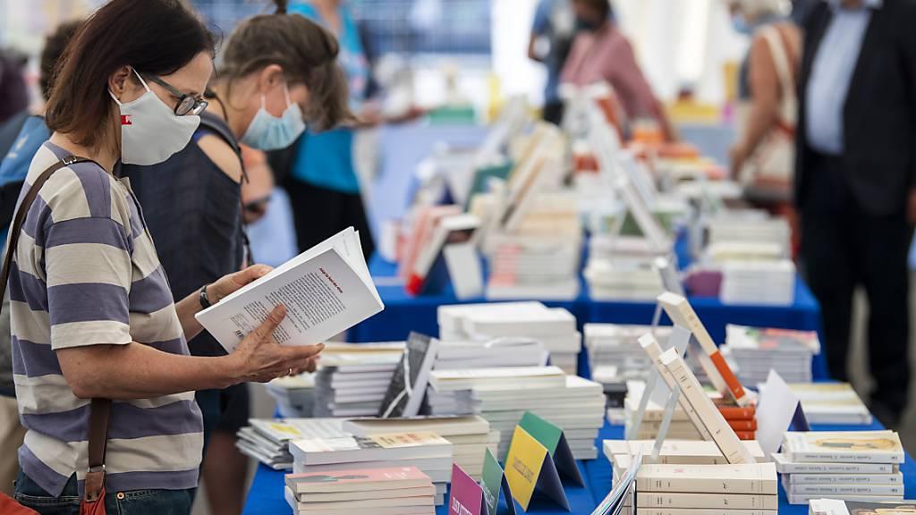 Bücherkauf mit Maske. Dem Bundesamt für Gesundheit sind innerhalb eines Tages 444 neue Corona-Fälle gemeldet worden. (Archivbild)