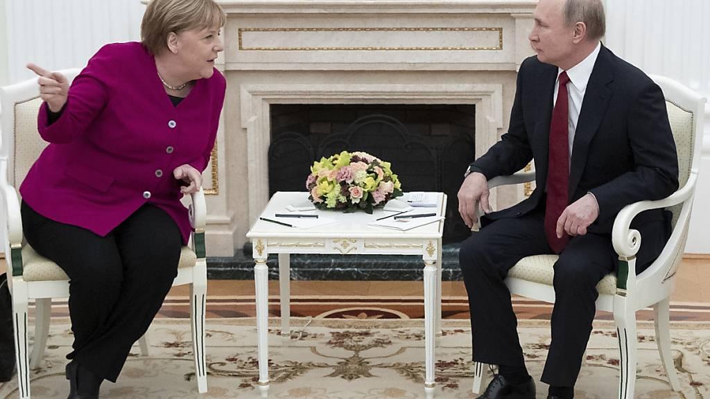 ARCHIV - Bundeskanzlerin Angela Merkel und der russische Präsident Wladimir Putin unterhalten sich im Kreml. Foto: Pavel Golovkin/AP/dpa