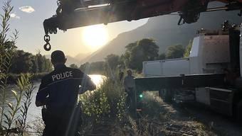 Walliser Kantonspolizisten bei der Bergung des Autowracks aus der Rhone. Nun steht fest, dass im Auto ein Mann und ein Mädchen gesessen hatten, die seit einem Unwetter vermisst werden.