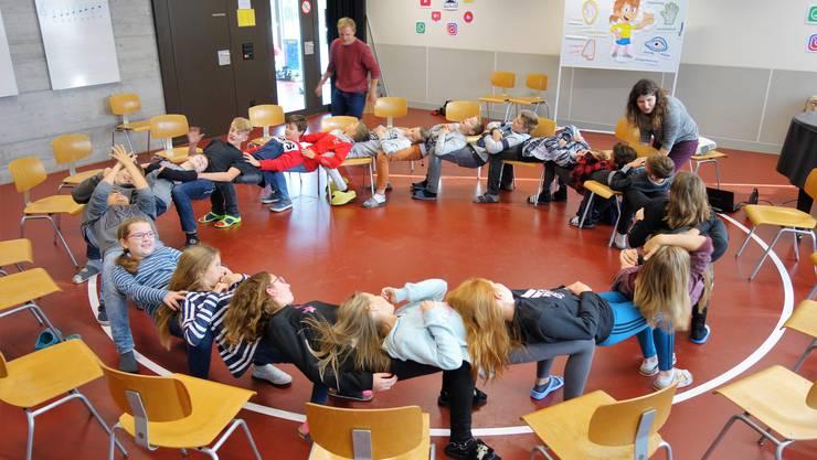 Es funktioniert: Wenn alle mitmachen, fällt der Kreis nicht zusammen, auch wenn alle Stühle weggeschoben werden.