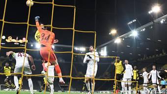 Die Szene des Spiels: Cluj-Goalie Cristian Balgradean faustet vor YB-Verteidiger Cédric Zesiger den Ball weg.