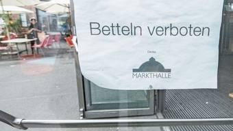 Ein abgeklebtes Stück Papier am Eingang weist auf das Bettelverbot in der Markthalle Basel hin.