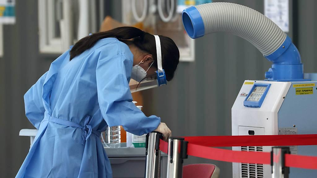 Eine medizinische Mitarbeiterin einer Corona-Teststation steht in Seoul vor einem Luftkühler. Zuletzt wurden im Land 826 neue Infektionen gemeldet, der höchste Wert seit fast sechs Monaten. Foto: --/YNA/dpa
