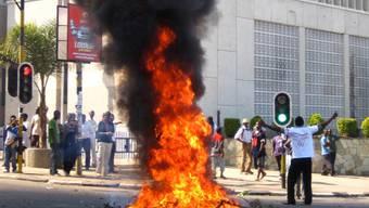 Aus Protest gegen die Regierung verbrennt ein Mann in Malawis Hauptstadt Lilongwe grüne Äste auf der Strasse