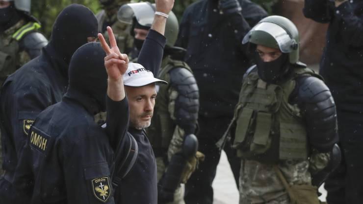 Ein Demonstrant zeigt ein Siegeszeichen während eines Protests vor Polizisten. Die belarussische Sonderpolizei OMON ging in der Nacht in der Hauptstadt gegen friedliche Demonstranten vor. Foto: Sergei Grits/AP/dpa