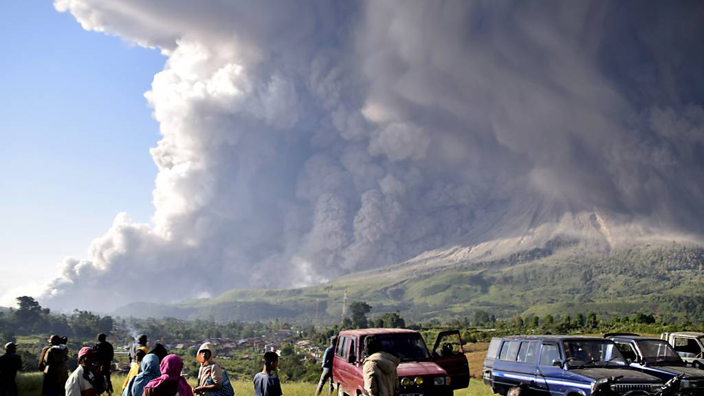 dpatopbilder - Menschen beobachten eine Eruption des Vulkans Sinabung in Karo. Foto: Uncredited/AP/dpa