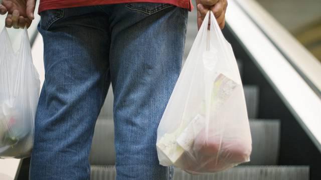 Ein Mann trägt zwei Wegwerf-Plastiksäcke - diese sollen verboten werden, verlangt eine vom Nationalrat angenommene Motion (Archiv)