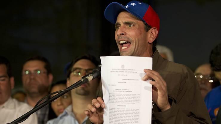 Venezuelas Oppositionspolitiker Henrique Capriles zeigt das Dokument, das ihn für 15 Jahre von einer Kandidatur ausschliessen soll.