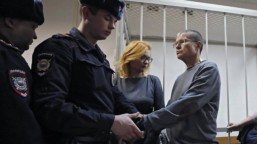 Ein Polizist legt dem Alexej Uljukajew im Gericht Handschellen an - der russische Ex-Wirtschaftsminister wurde wegen der Annahme von Schmiergeld verurteilt.
