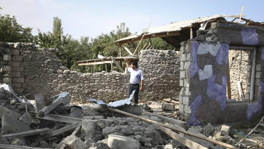 Ein Mann steht in den Ruinen eines Hauses, das angeblich während der Kämpfe beschädigt wurde.