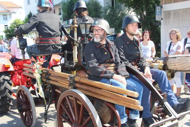 Ein antikes Feuerwehr-Fahrgerät rattert im Umzug mit.